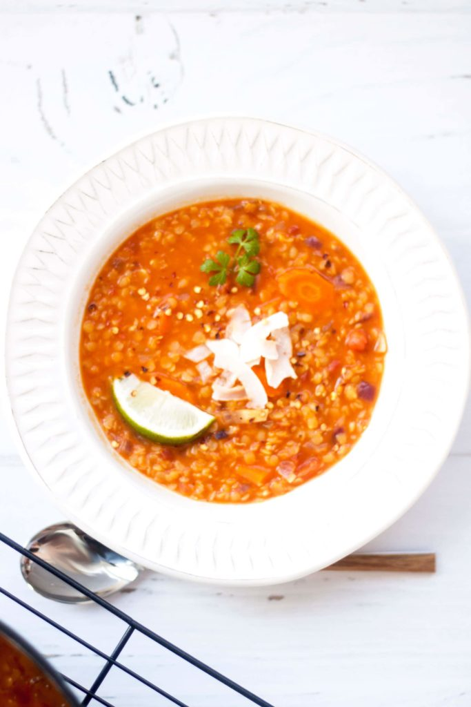 vertical photo of Red Lentil Coconut Soup in white plate on a white background