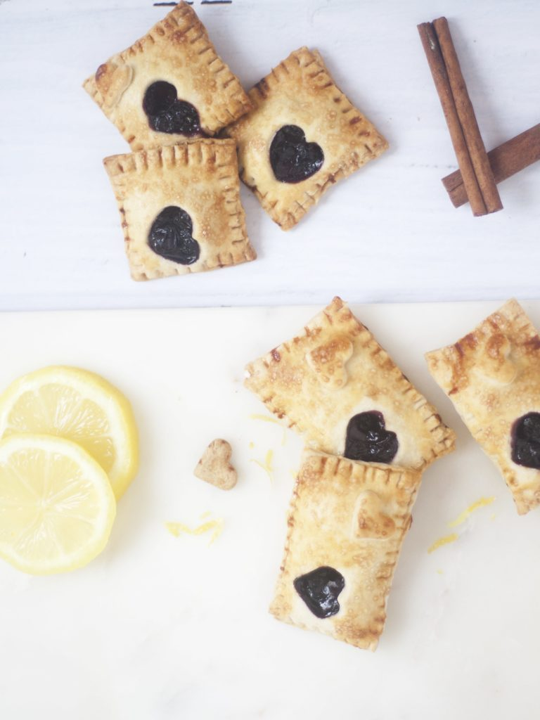 Blueberry and Lemon Hand Pies on a white background surrounded by lemon slices and cinnamon sticks