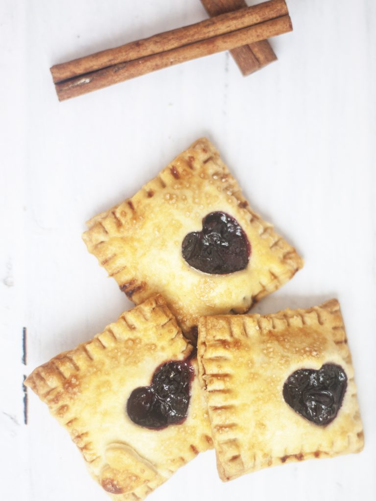 Blueberry and Lemon Hand Pies on a white background with cinnamon sticks