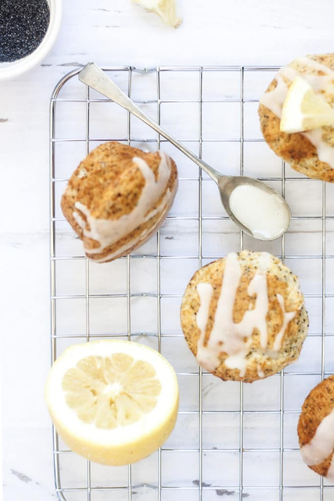 Eggless Lemon Poppyseed Yogurt Muffins on cooling rack on a white background