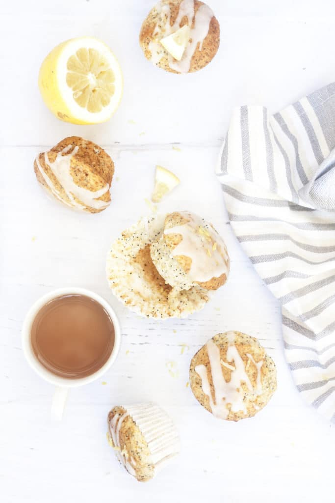 Eggless Lemon Poppyseed Yogurt Muffins on a white background surrounded by tea towel and tea