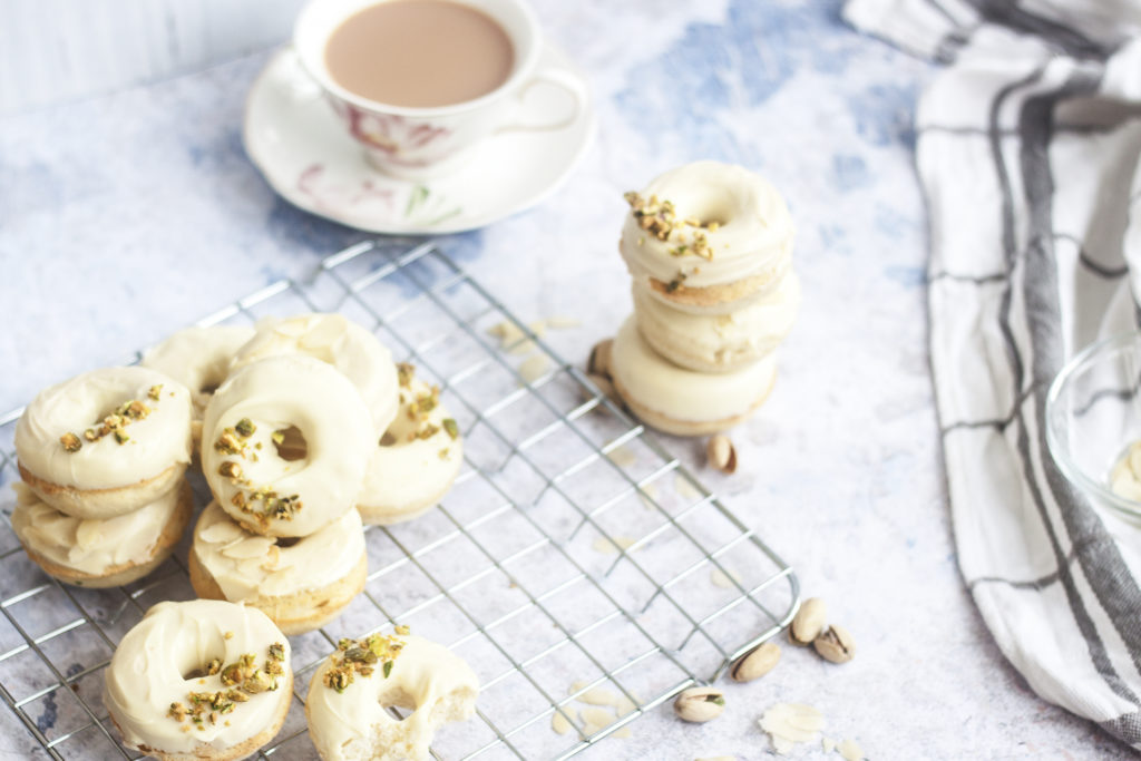 White Chocolate Ricotta Donuts stacked and on a wire rack surrounded by pistachios, almonds, and a cup of tea.