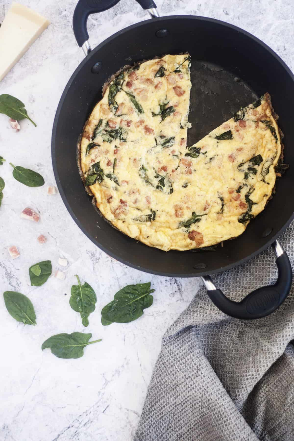 Pancetta Spinach and Cheese Frittata in skillet missing one slice