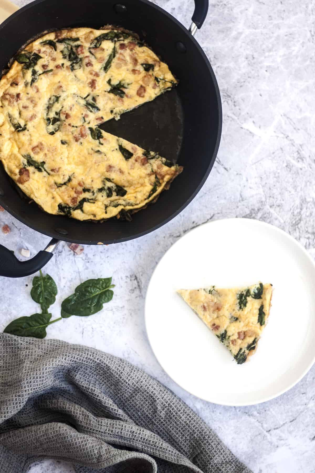 Pancetta Spinach and Cheese Frittata in skillet with missing wedge