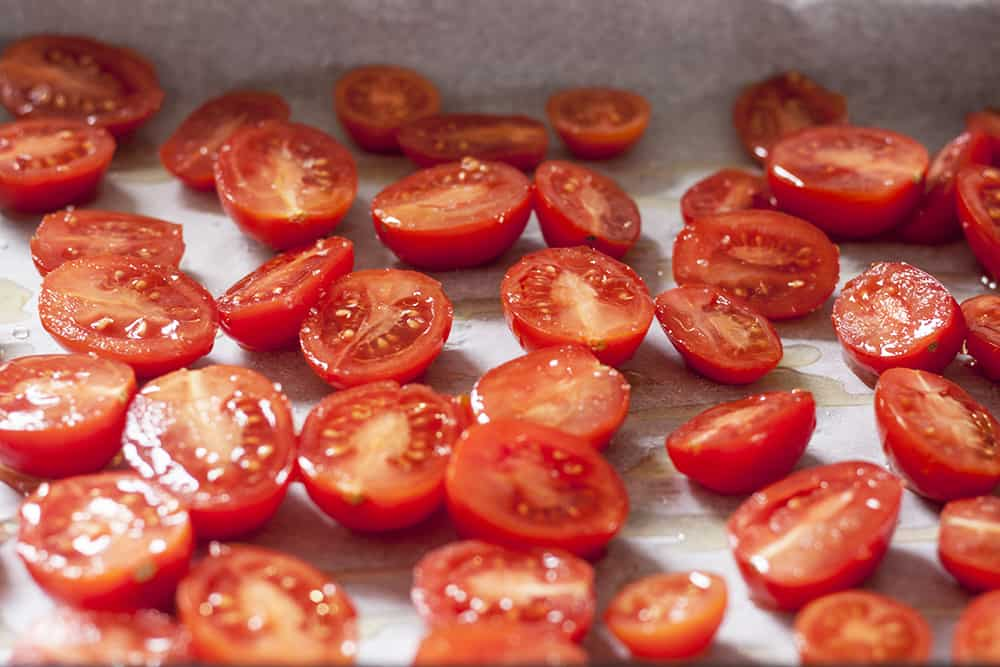 cherry tomatoes sliced in half lengthwise on a baking sheet drizzled with olive oil