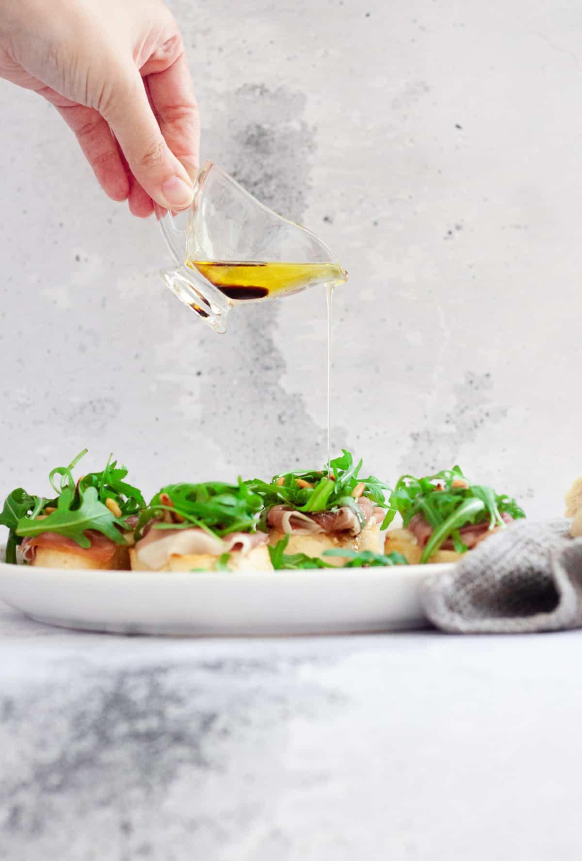 Prosciutto, Brie and Arugula Bruschetta drizzled with balsamic vinaigrette