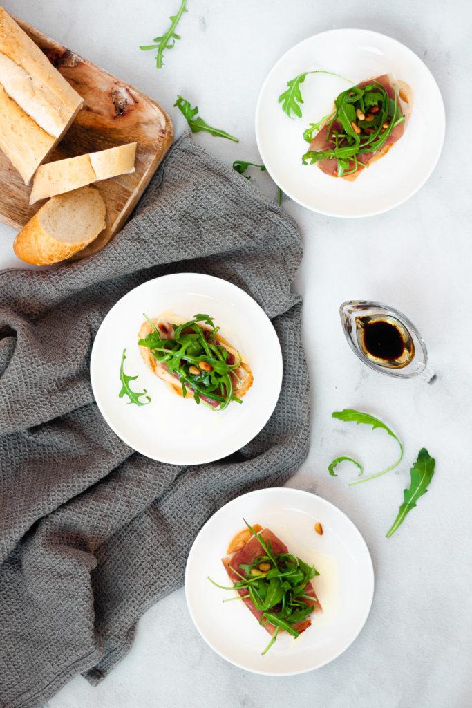 Prosciutto, Brie and Arugula Bruschetta on white plates