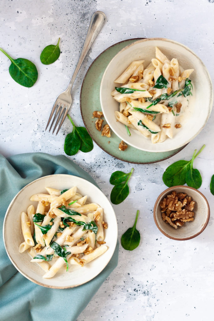 vertical image of creamy spinach and walnut pasta plates