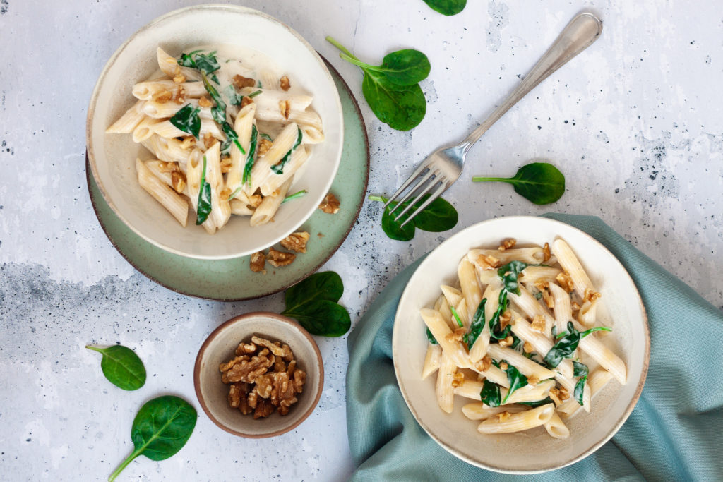 two plates of creamy spinach and walnut pasta