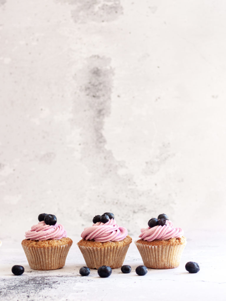 three Earl Grey Cupcakes with Blueberry Frosting