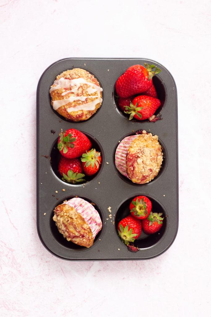eggless strawberry swirl muffins in muffin tray with fresh strawberries