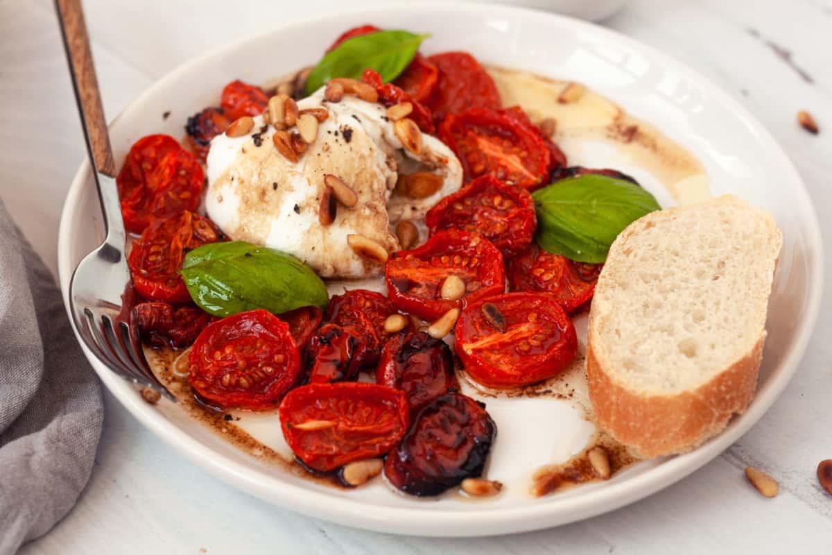 Roasted Tomatoes, Buffalo Mozzarella and Pine Nut Appetizer on white plate