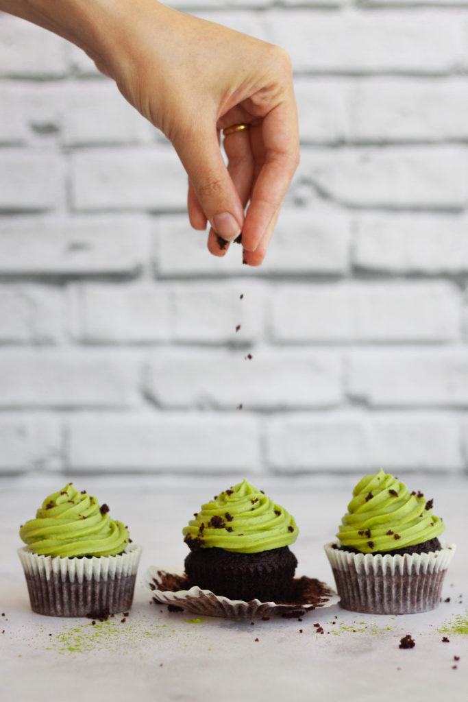sprinkling matcha chocolate cupcakes with chocolate crumbs