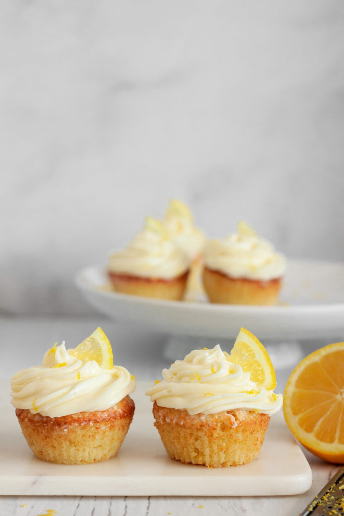 Limoncello Cupcakes with Mascarpone Lemon Frosting and a slice of lemon on a white background