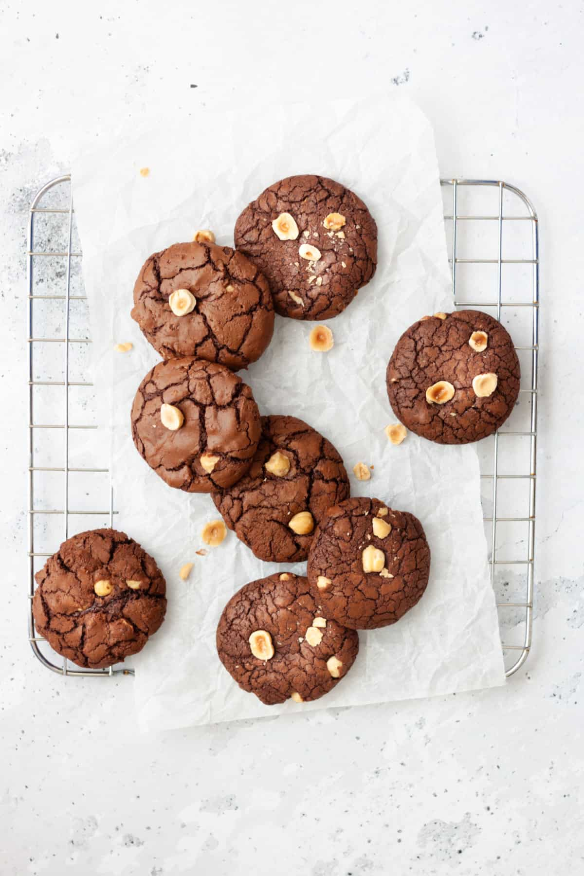 hazelnut brownie cookies on parchment paper and wire rack on a white background/