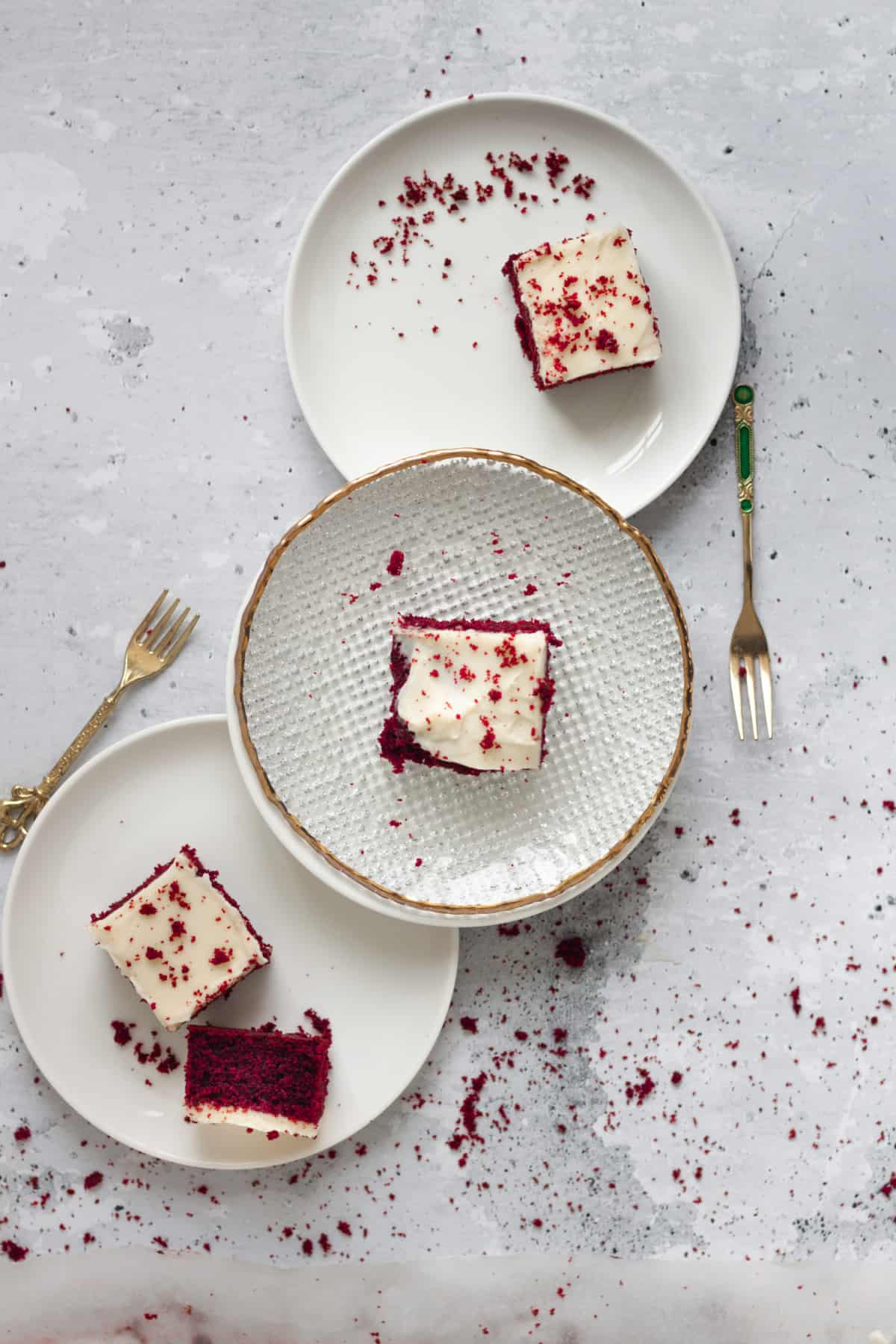 three squared of Red Velvet Sheet Cake with Mascarpone Cream Cheese Frosting on three plates