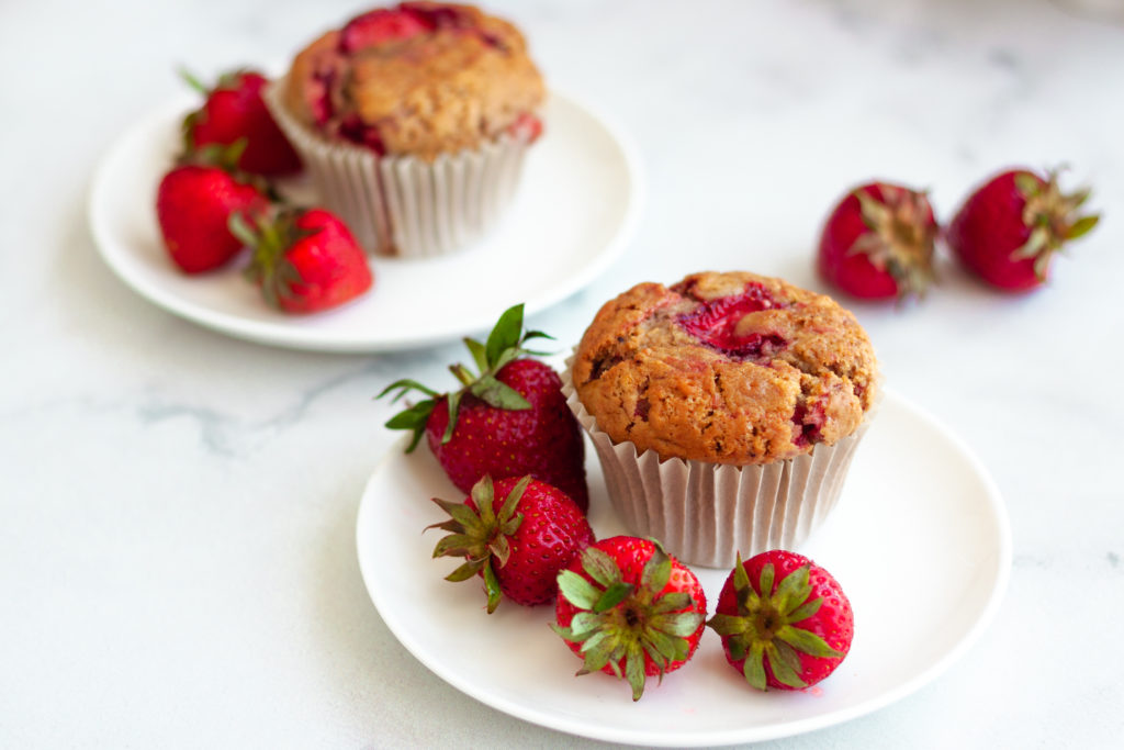 vegan strawberry muffins on a dessert plate surrounded by fresh strawberries