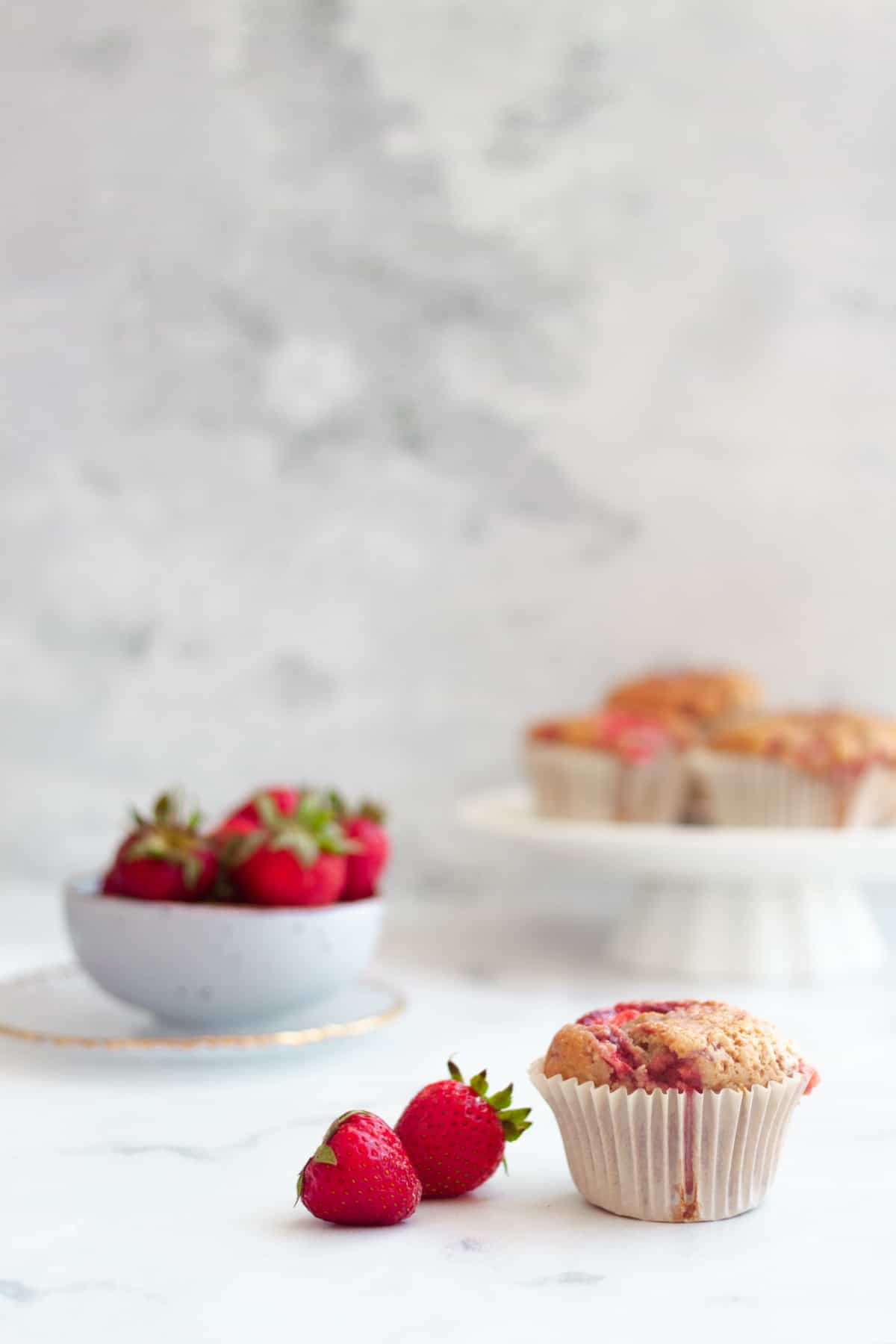 one strawberry muffin next to 2 fresh strawberries and more strawberries in  a bowl in the background.