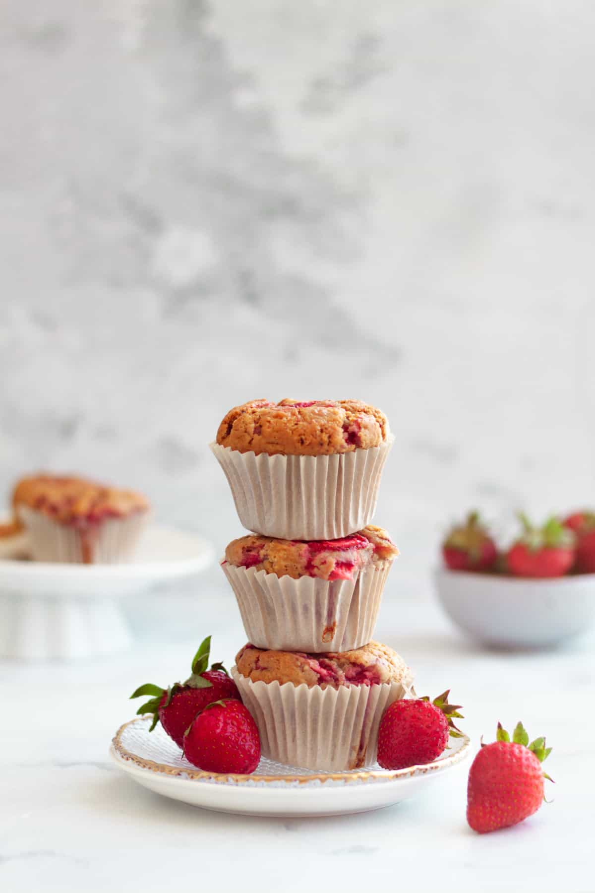 a stack of 3 strawberry muffins surrounded by fresh strawberries on a white background.
