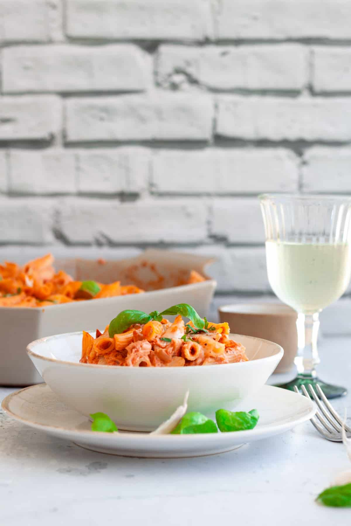 A single serving of Baked Goat Cheese Pasta in a white plate next to fresh basil leaves and a glass of wine.