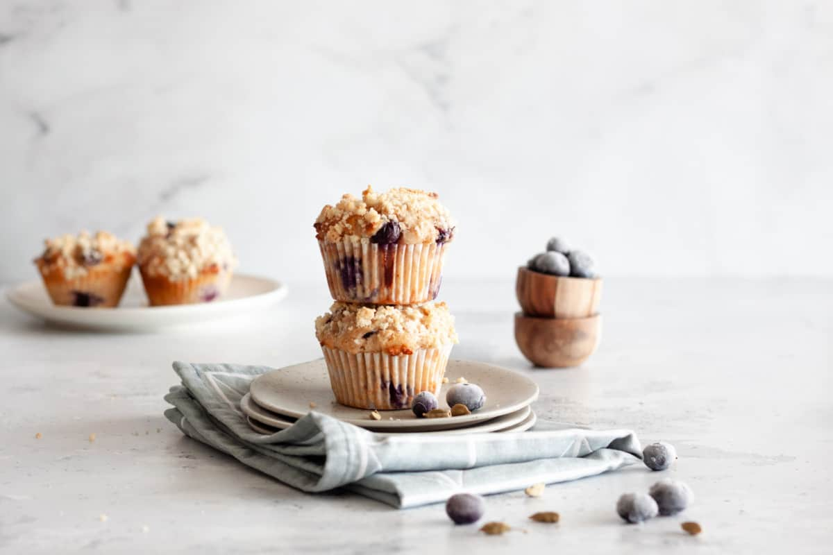 two blueberry cardamom muffins stacked on top of each other on a dessert plate