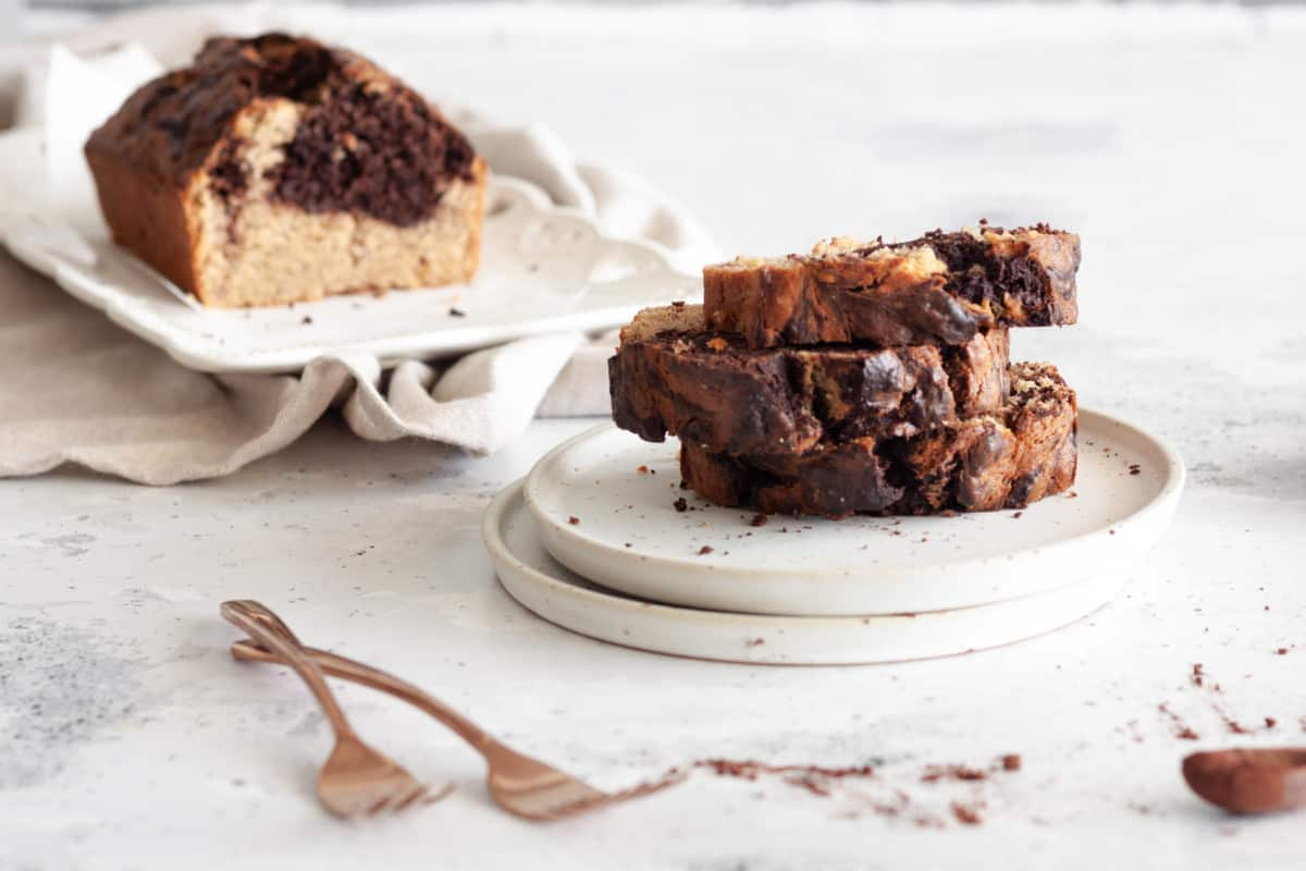 three slices of Chocolate Banana Marble Loaf Cake stacked on a dessert plate