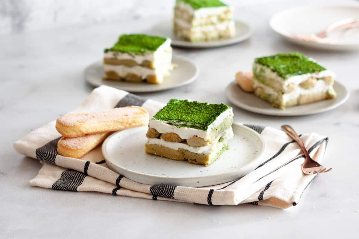 multiple servings of eggless matcha tiramisu on dessert serving plates