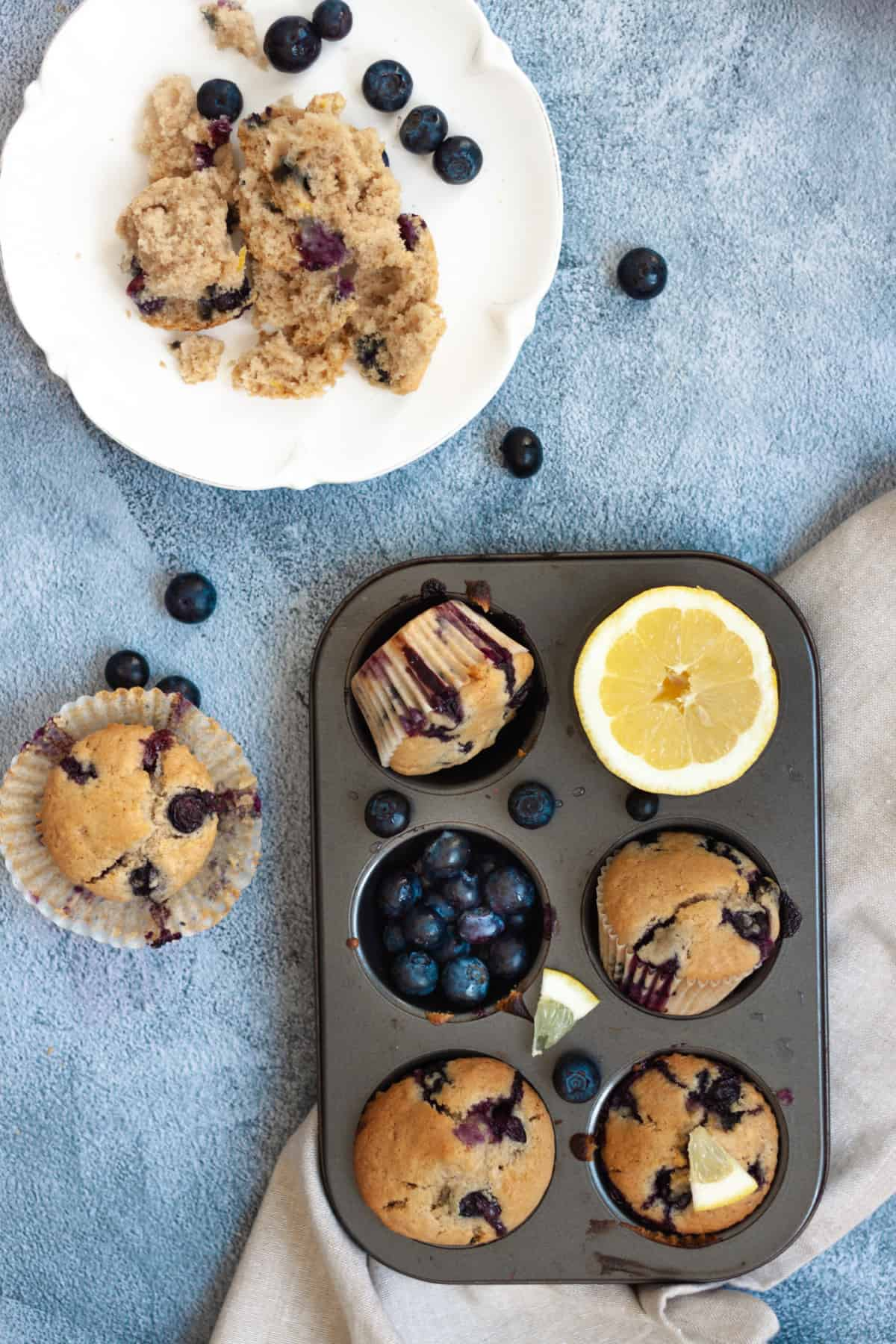 vegan blueberry lemon muffins in muffin tray with lemon and fresh blueberries