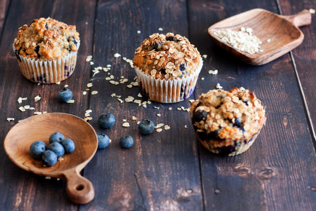 three Blueberry Banana Oatmeal Muffins on a wooden background