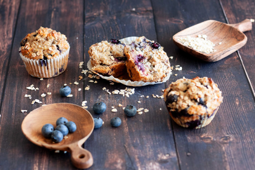 three Blueberry Banana Oatmeal Muffins, one of which is cut in half.