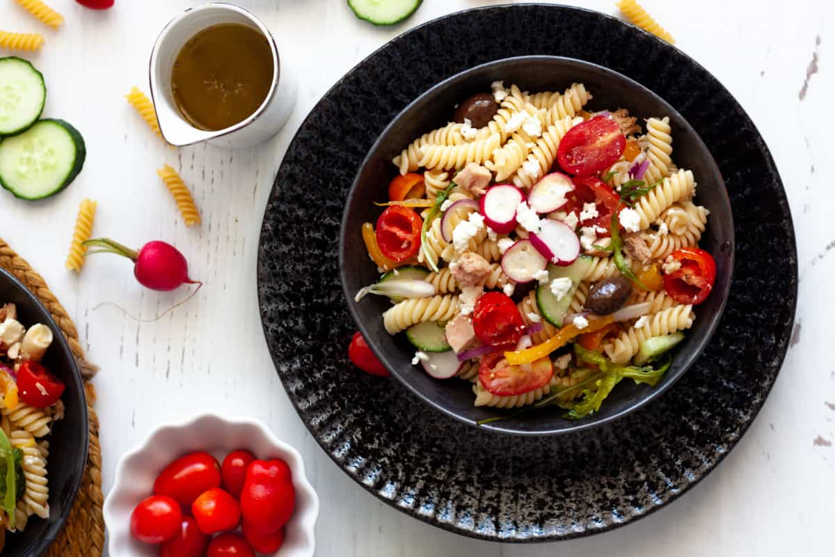 A serving of Mediterranean-Style Tuna Pasta Salad in a black plate