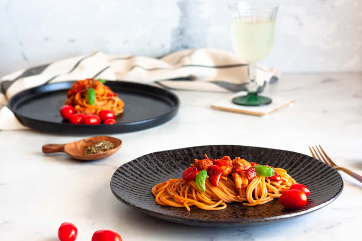 two servings of Prawn Bisque Pasta in black plates on a white background