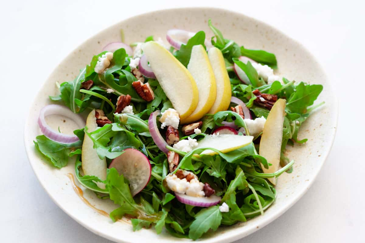 arugula, pear, and pecan salad serving in a white plate
