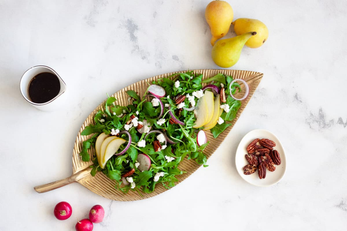 arugula, pear, and pecan salad on a gold plate