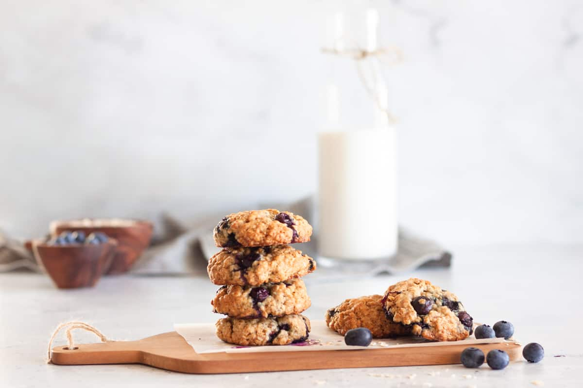 a stack of blueberry oatmeal cookies on a brown serving board.