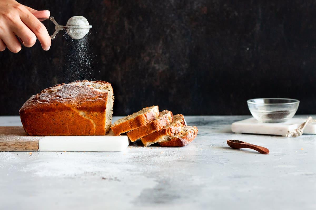 sprinkling powdered sugar on loaf cake