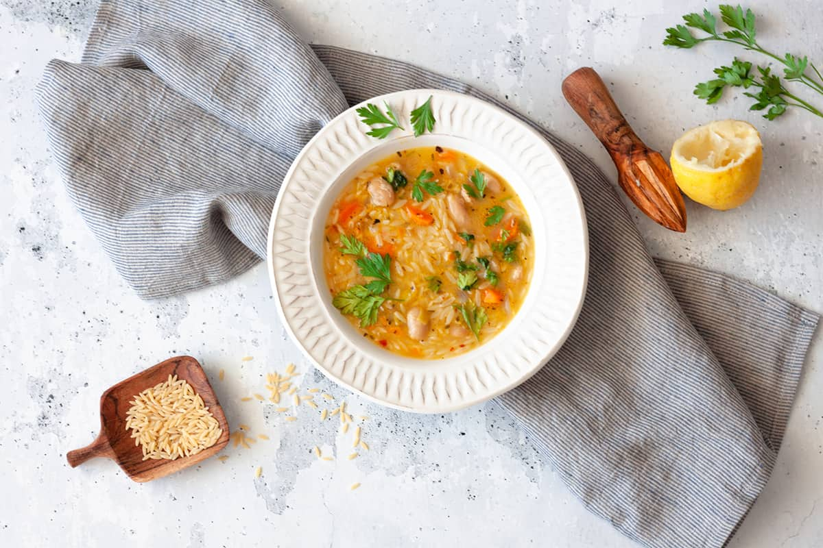 a plate of Vegan Orzo Soup on striped linen